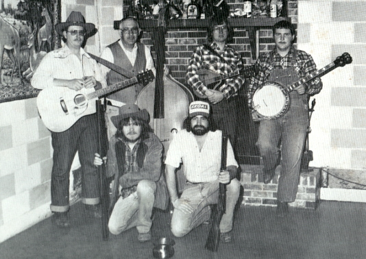 "This is the photo from the back cover of the Beaucoup Bottom Boys' 1981 LP, ""Comin Out."" Kneeling in front are Steven ""Butch"" Kosma (acoustic guitar and vocals) and David Lee Halstead (acoustic guitar, mandolin and vocals). Behind them are Bob Juhl (acoustic guitar and vocals), Marv Juhl (bass), Don Willi (fiddle) and Joe Juhl (banjo). Steve Townes (not pictured) played harmonica with the band. (Photo by John Meacham)"